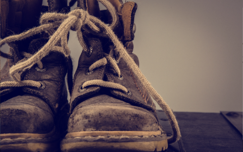 Close up of old construction boots on gray background